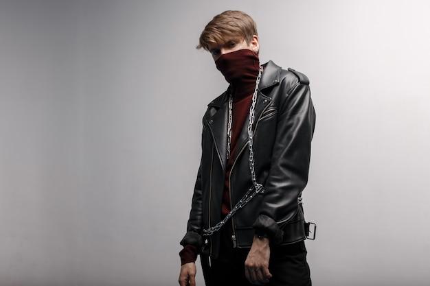 Schattige jonge man met bourgondische trendy golf in een vintage jas van zwart leer in zwarte stijlvolle jeans en metalen ketting, permanent en poseren binnenshuis tegen een witte muur. stijlvolle knappe jongen.