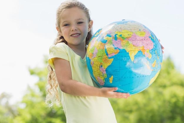 Schattige jonge meisje houdt van de globe op park