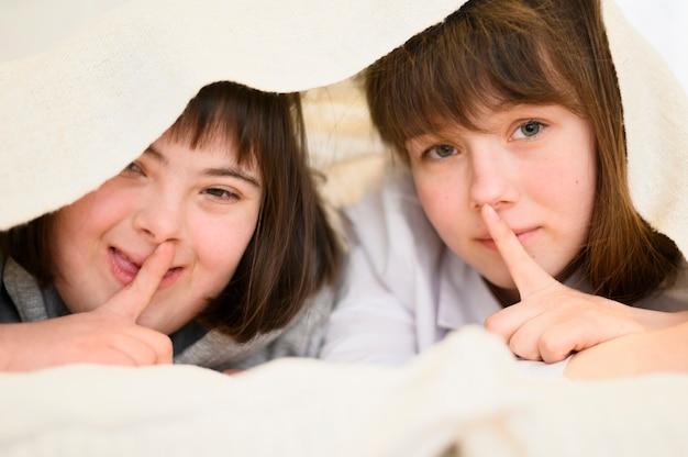 Schattige jonge meisjes samen verbergen