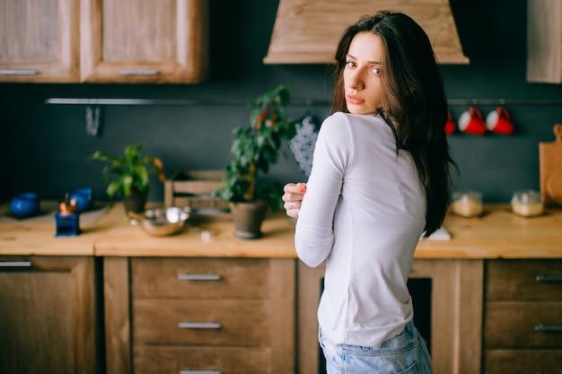 Schattige jonge model met sensuele gepassioneerde gezicht, donker lang haar poseren op keuken.