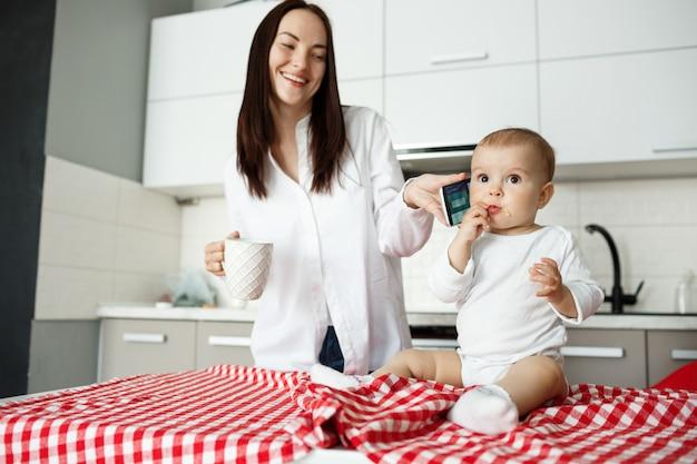 Schattige jonge moeder die telefoon geeft aan baby en glimlacht