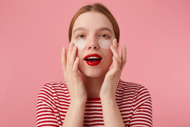 Schattige jonge roodharige vrouw in een rood gestreept t-shirt, met rode lippen, raakt zijn gezicht aan met de vingers, kijkt en verwacht magische werking van vlekken uit donkere kringen onder zijn ogen.