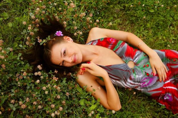 Schattige jonge roodharige vrouw liggend op grasveld in het park
