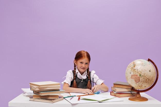 Schattige jonge schoolmeisje met rood haar in schooluniform kijken naar voren, tekenen en zittend aan tafel op geïsoleerde muur