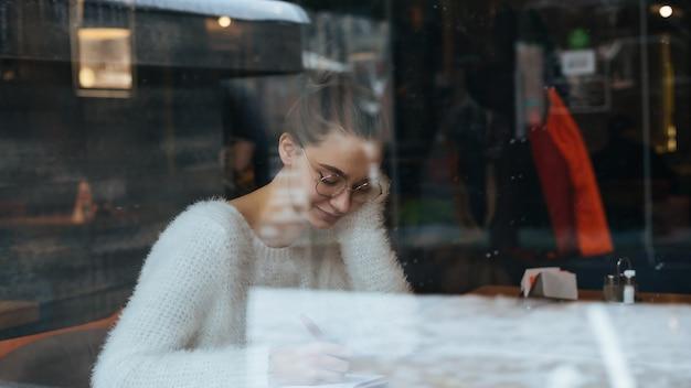 Schattige jonge studente in een witte trui en bril zit in een café, schrijft iets in een notitieboekje