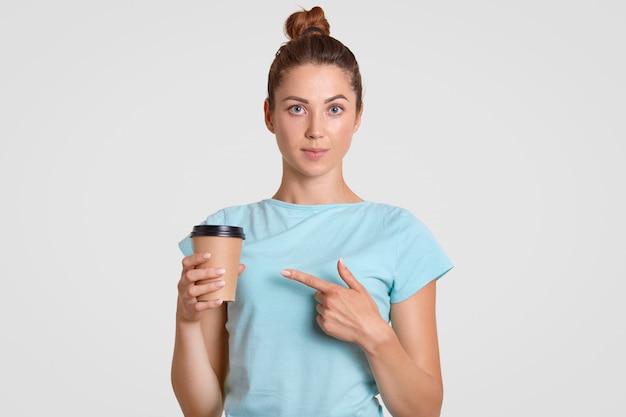 Schattige jonge tiener biedt u koffie of cappuccino uit een wegwerpbeker