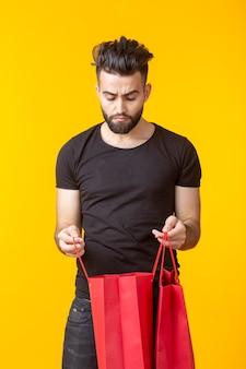 Schattige jonge triest bebaarde man kijkt naar de aankoop in boodschappentassen op een gele ondergrond met kopie