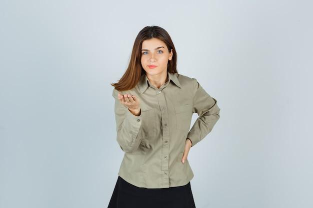 Schattige jonge vrouw die de hand uitrekt in een vragend gebaar in shirt, rok en er serieus uitziet. vooraanzicht.