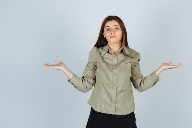 Schattige jonge vrouw die hulpeloos gebaar toont door haar schouders op te halen in shirt, rok en verward, vooraanzicht.