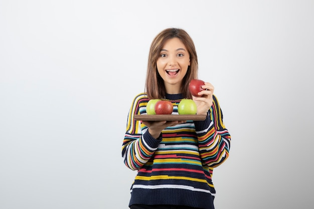 Schattige jonge vrouw die in vrijetijdskleding een bos appels houdt.