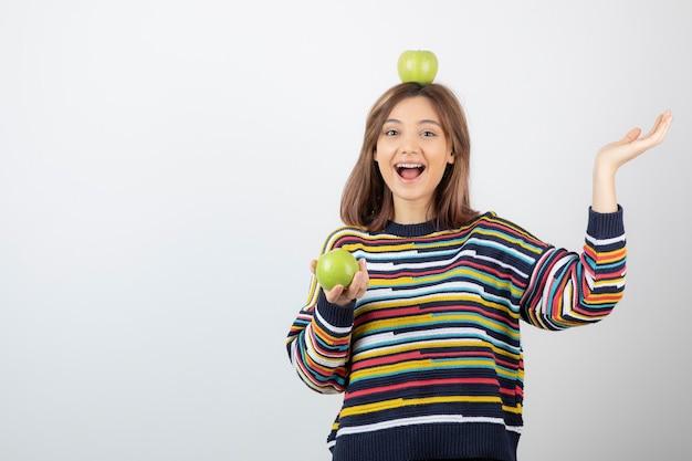 Schattige jonge vrouw die in vrijetijdskleding groene appels op witte achtergrond bekijkt.