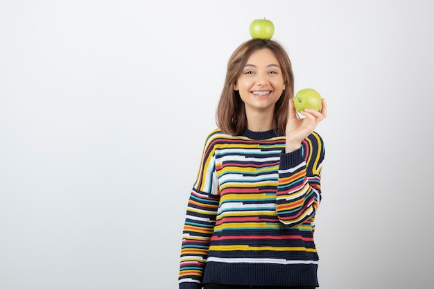 Schattige jonge vrouw die in vrijetijdskleding groene appels op witte achtergrond houdt.