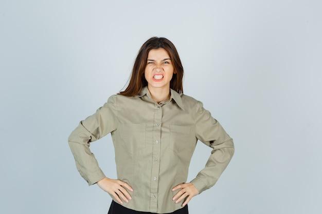 Schattige jonge vrouw hand in hand op taille, tanden op elkaar klemmen in shirt en er agressief uitzien, vooraanzicht.