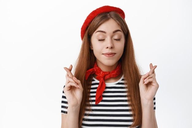 Schattige jonge vrouw in mooie hoed, ogen dicht en vingers gekruist voor geluk, wensen doen, hopen dat er iets gebeurt, bidden, over de witte muur staan