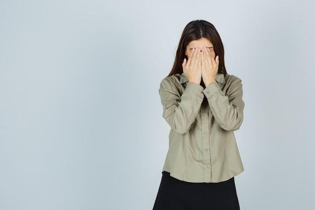 Schattige jonge vrouw in shirt, rok die gezicht bedekt met handen en depressief kijkt, vooraanzicht.
