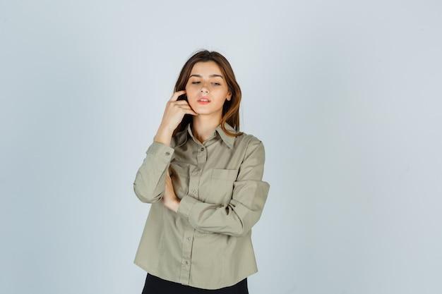 Schattige jonge vrouw in shirt, rok die haar wang aanraakt terwijl ze naar beneden kijkt en er attent uitziet, vooraanzicht.