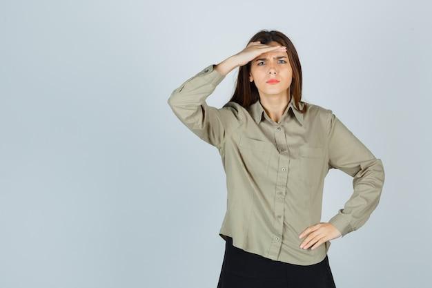 Schattige jonge vrouw in shirt, rok die hand boven het hoofd houdt en er verward uitziet, vooraanzicht.