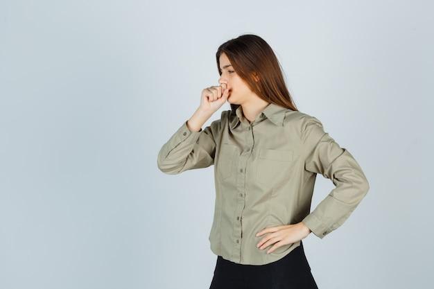 Schattige jonge vrouw in shirt, rok die lijdt aan hoest en er ziek uitziet, vooraanzicht.