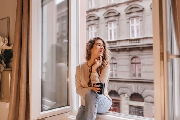 Schattige jonge vrouw in trendy spijkerbroek genieten van vrije tijd thuis met kop warme chocolademelk