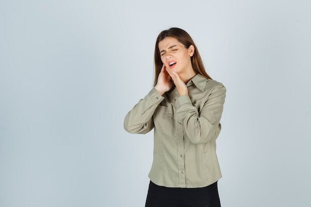Schattige jonge vrouw lijdt aan kiespijn in shirt, rok en ziet er pijnlijk uit, vooraanzicht.