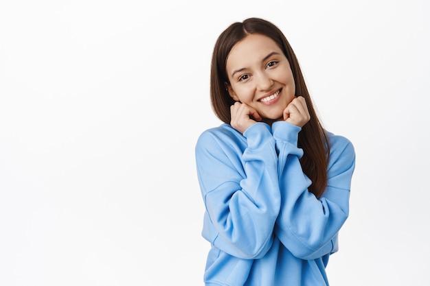 Schattige jonge vrouw met een kokette, gelukkige glimlach, kantelend hoofd, haar gezicht aanraken en blozen, flirten, staren en nadenken over een mooie, witte muur.