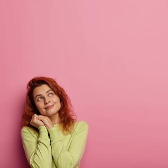 Schattige jonge vrouw met golvend rood haar, kijkt naar boven en herinnert zich hoe vriend haar kuste, de handen bij elkaar houdt in de buurt van het gezicht, heeft een lichte glimlach, draagt een groene trui
