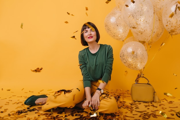 Schattige jonge vrouw met kort haar sparkle confetti kijken. blij vrouwelijk model in trendy kleding, zittend naast helium ballonnen.