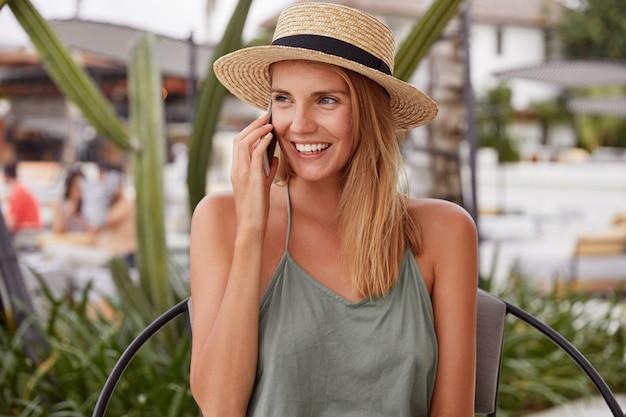 Schattige jonge vrouw met positieve uitdrukking, nonchalant gekleed, heeft telefoongesprek, gekleed in zomerhoed, zit op stoel buiten, onder de indruk na een wandeling over prachtig strand