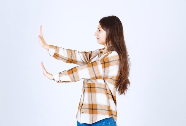 Schattige jonge vrouw permanent en doen stopbord op witte muur.