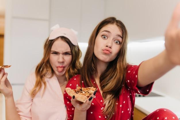 Schattige jonge vrouw pizza eten en gek rond. positieve zussen die plezier hebben en genieten van hun favoriete fastfood.