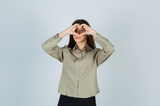 Schattige jonge vrouw toont hartgebaar in shirt, rok en ziet er vrolijk uit, vooraanzicht.