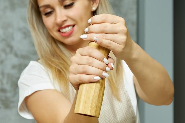 Schattige jonge vrouwelijke chef-kok zet kruiden zout peper