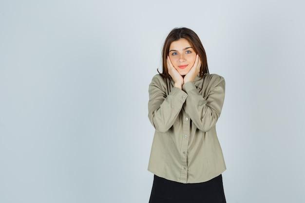 Schattige jonge vrouwelijke kussen gezicht op haar handen in shirt, rok en beschaamd, vooraanzicht.