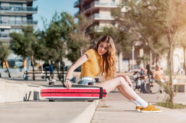 Schattige jonge vrouwelijke skater zittend op de trap met haar lange board skate