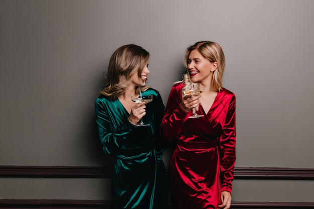 Schattige jonge vrouwen die ergens over praten en wijn drinken. blije dames die van feest genieten.