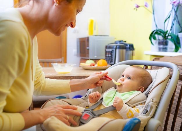 Schattige jonge zorgzame blanke moeder voedt haar charmante dochtertje van zes maanden in een gezellige woonkamer