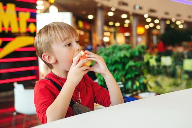 Schattige jongen appel eten in moderne café. een gelukkige en gezonde jeugd. grappige jongen met appel, zittend aan tafel.