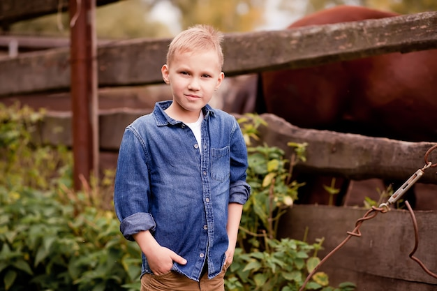 Schattige jongen cowboy permanent in de buurt van houten hek met paarden
