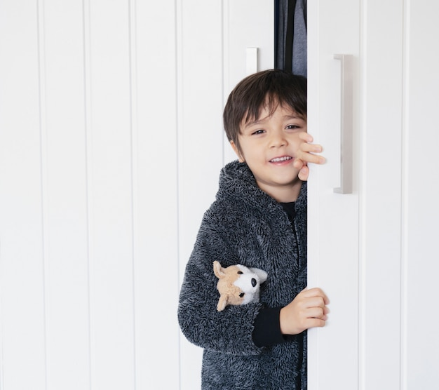 Schattige jongen draagt pluizige pyjama knuffelen hond speelgoed spelen verstoppertje in de kast