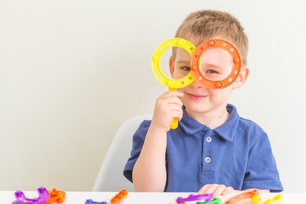 Schattige jongen gemaakt glazen plastic blok speelgoed en glimlachen. ruimte kopiëren. horizontale foto van grappige peuter