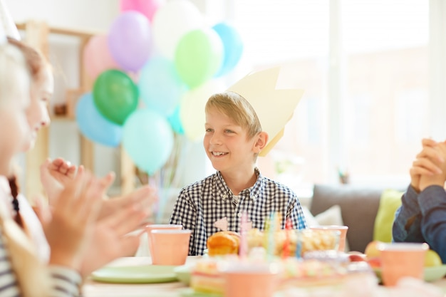 Schattige jongen glimlachend op verjaardagsfeestje