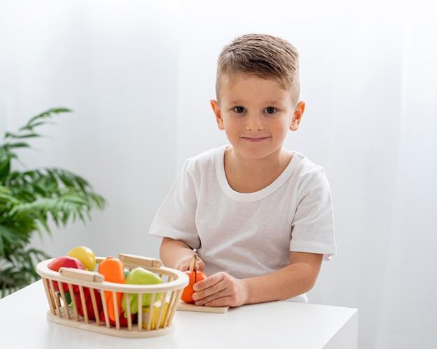 Schattige jongen groenten snijden