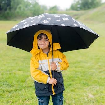 Schattige jongen in regenjas en paraplu