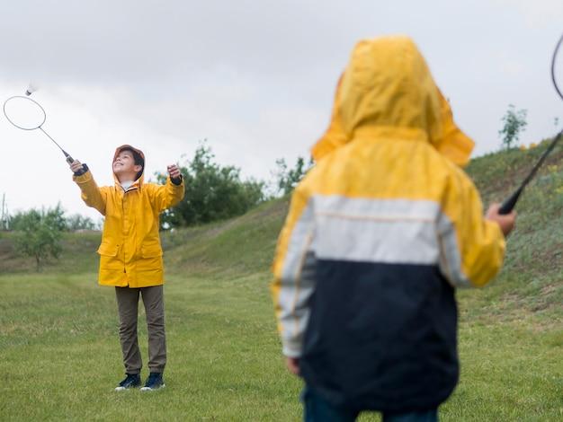 Schattige jongen in regenjas spelen met zijn broer