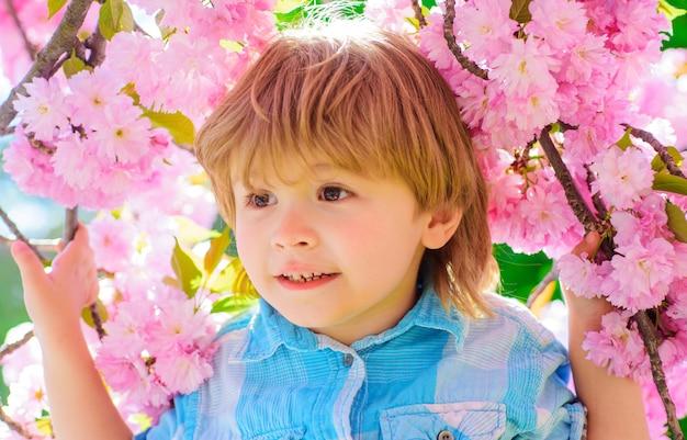 Schattige jongen in roze bloemen.