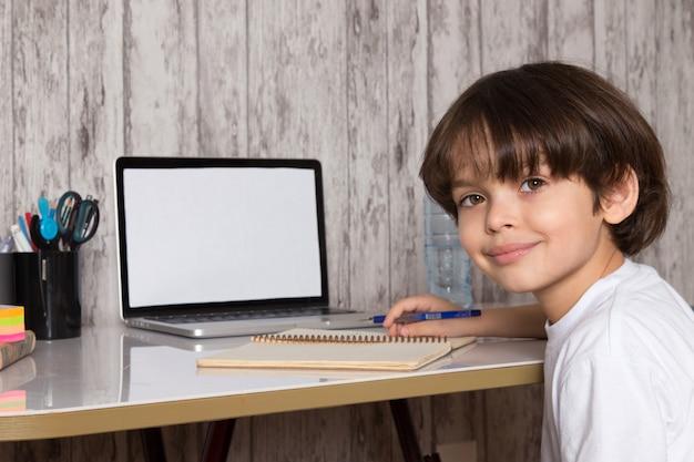 Schattige jongen in wit t-shirt met behulp van grijze laptop