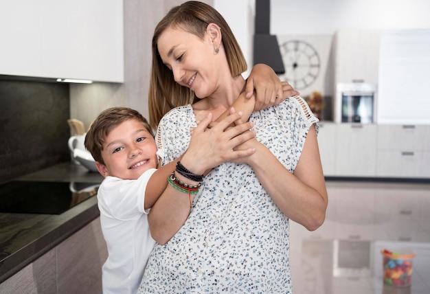 Schattige jongen knuffelen zijn moeder thuis