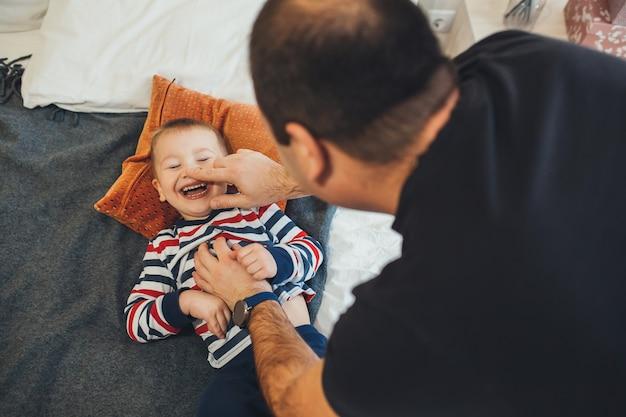 Schattige jongen lachen met gesloten ogen liggend op het bed terwijl zijn vader speelt met hem zijn neus aanraken. vader speelt 's ochtends met zijn zoontje.