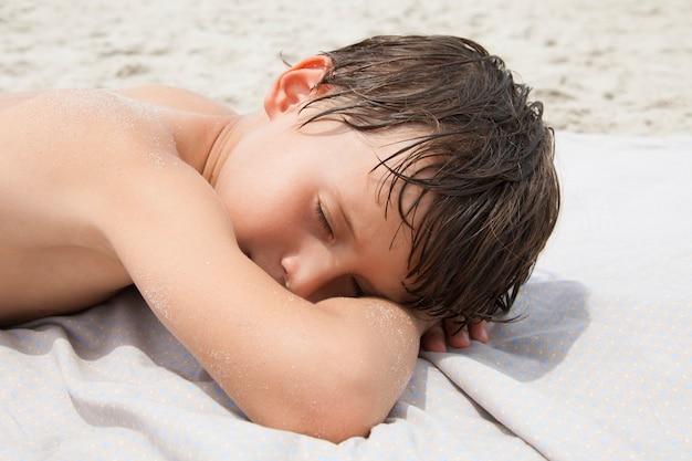 Schattige jongen liggend op het strand en zonnebaden. kind rusten op een strand op een zonnige dag.