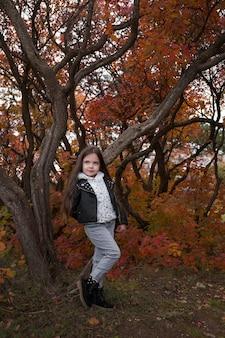 Schattige jongen meisje 4-5 jaar oud trui en jas dragen in park. camera kijken. herfstseizoen. jeugd. modieuze stijlvolle en charmante kleine dame Premium Foto